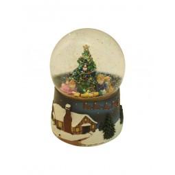 Sfera con brillantini e bambini sotto l'albero di Natale